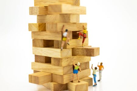 Miniature people : Group Athletes climb on wooden block wooden. Image use for Activities, travel, business concept.