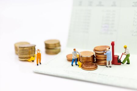 Miniature people : Workers and a pile of coins on a book bank for extend the progress, image use for stable growth growing progress Stock Photo - 144198117