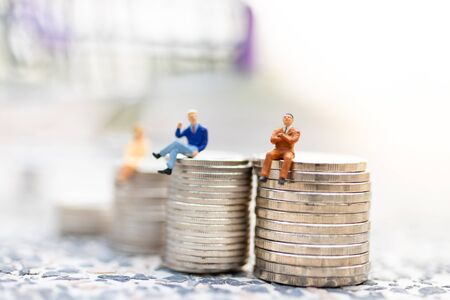 Miniature people : Businessman sitting on stack of coin . Image use for business concept.