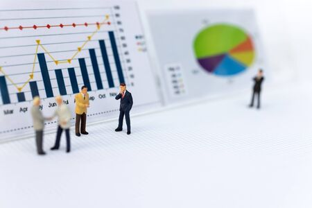 Miniature people : Businessmen earn profits from work, reference the graph to increase benefit. Image use for as a business concept. Banque d'images