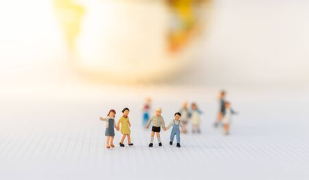 Miniature people: Group of children on white background. Image use for education,  preparing for opening day of study. Stock Photo