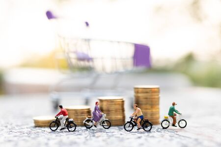 Miniature people : Travelers riding bicycle with stack of coins. Image use for background traveling and healthy, business concepts.