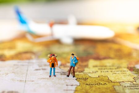Miniature people: travelers with backpack standing on world map travel by plane. Image use for travel business concept. Banque d'images