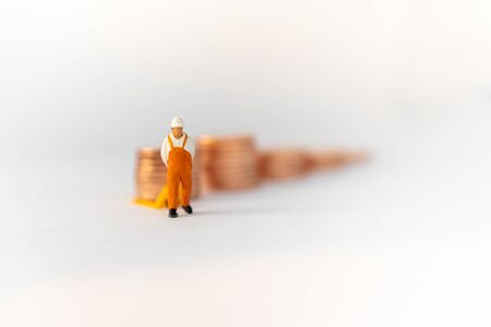 Miniature people: Worker use pallet truck with stack of coins. Image use for background business concept.