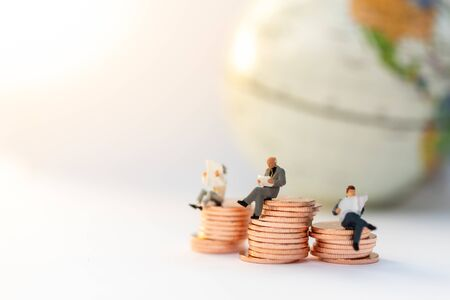 Miniature people:  Businessman sitting on the stack of coins. Image use for business concept.