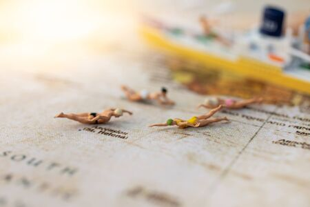 Miniature people : Young in swimsuit and friends swiming on world map. Image use for holiday, vacation concept.