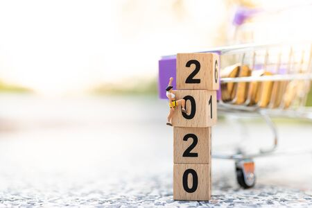 Miniature people: Traveler climbing on wooden block new year. Image use for retail business concept