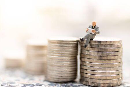 Miniature people : Businessman sitting on stack of coin . Image use for business concept. Stock Photo - 144775717