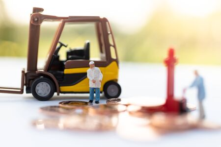 Miniature people: Worker use pallet truck with stack of coins. Image use for background business concept. Stock Photo - 144775722