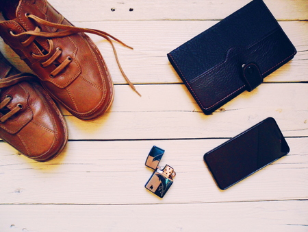 card holder: Brown leather mens shoes, black leather business card holder, a smartphone and a lighter