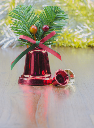 closed ribbon: Christmas ornament - red bells with defocused shimmering background on wooden board.