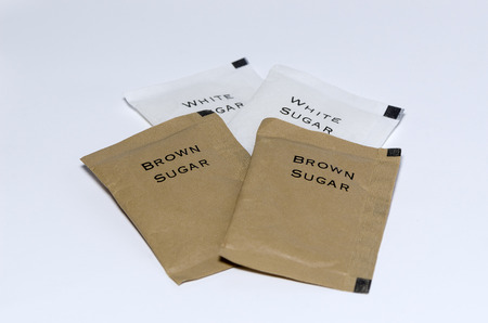 small paper: Small paper package of white and brown sugars on isolated white background.