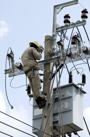 lineman: Electrician lineman at climbing work on electrical power pole for service and maintenance.
