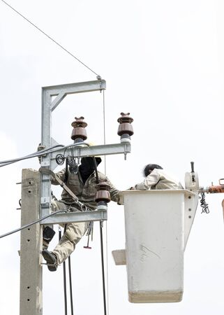 outage power: Two electrician are installing new cables of high voltage that one electrician is climbing on an electric power pole, another one  is on lift bucket