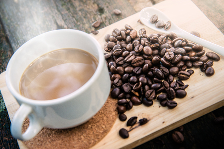 Hot cub of coffee and bean on wooden background