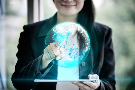 Businesswoman holding tablet with digital earth planet representing represents future technology concept