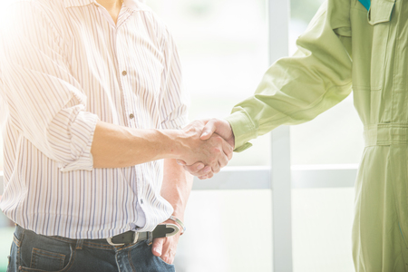 Engineer and architect shaking hands for successful deal in construction plan