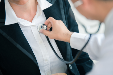 The doctor is listening to the patients heart with stethoscope