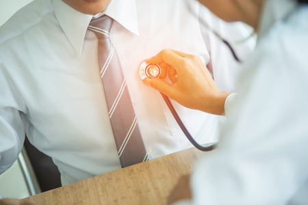 De arts luistert met een stethoscoop naar het hart van de patiënt Stockfoto