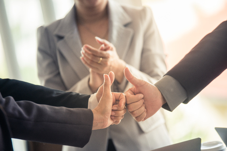 Hands of group business people showing thumbs up with the applause behind