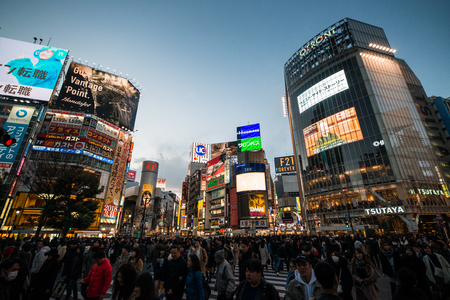 TOKYO, JAPAN - FEBRUARY 12, 2018: Shibuya scramble crossing in Tokyo at sunset, Shibuya Crossing is one of the busiest crosswalks in the world. Editorial