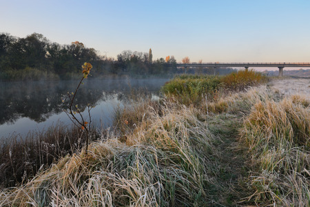 reveille: Cold morning landscape with a river. Grass covered by hoarfrost
