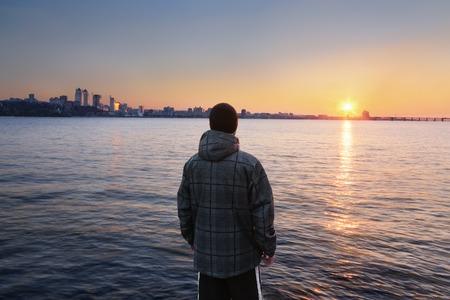 dnepr: The guy meets the sunset standing on the river bank and looking away into the city Stock Photo