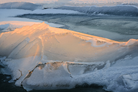 A beautiful epic ice crystal on the snow in the rays of the setting sun. Stock Photo