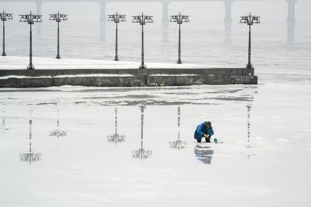frozen lake: The fisherman is fishing on the ice of a frozen river in an early foggy morning. Dnepropetrovsk, Ukraine Stock Photo