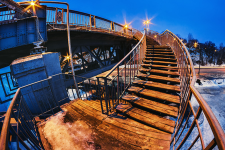 low perspective: Deserted pedestrian bridge at night in the lighting of street lamps. Monastyrskyj island Dnepropetrovsk city, Ukraine
