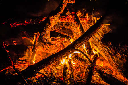 heart heat: Close up photo of the heart of a campfire.  The heat can be seen in the glow from the red hot embers.