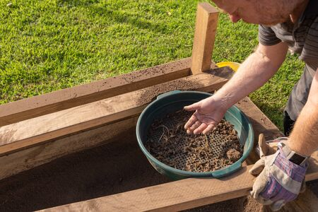 Sifting soil through a garden sieve to remove rubbish