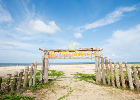 An image of wooden gate on the beach in blue sky and some clouds, Chumphon Province, Thailand