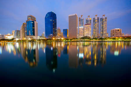 benjakitti: Bangkok, Thailand - July 5, 2015: Cityscape view of modern buildings at Benjakitti garden at twilight in Bangkok, Thailand, light of the lamps was shining on the road and buildings.  There were the building shadows on the lake. Editorial