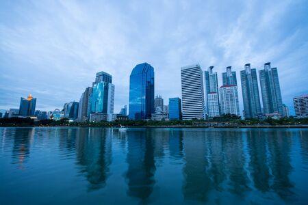 benjakitti: Bangkok, Thailand - July 5, 2015: Group of modern buildings near the lake at Benjakitti Park were under the rain clouds at twilight in Bangkok, Thailand