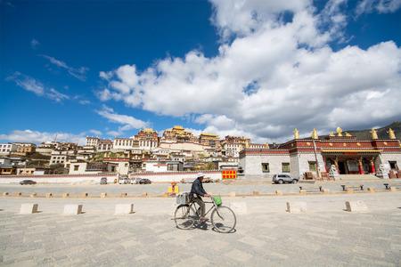 shangrila: Shangri-la, China - October 24, 2015:  A man was biking in front of Songzanlin Monastery in Shangri-la, Yunnan Province, China Editorial
