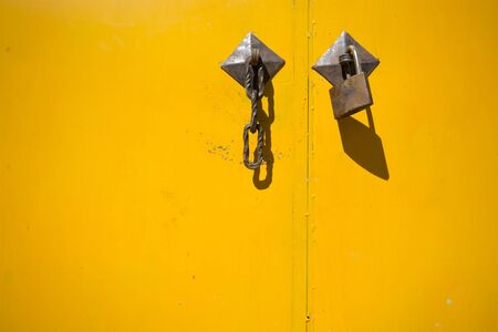 lock: Closed yellow doors with lock and shadow of lock
