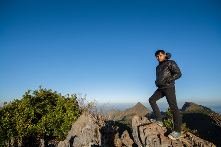 southeast asian: Mountain top with young southeast asian man in blue sky and clouds background