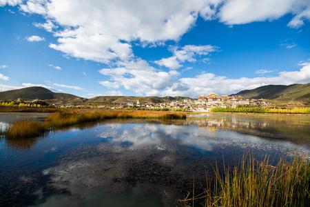 monasteri: Il lago e il tempio nella priorità bassa del cielo blu, contea di Shangri-La, provincia di Yunnan, Cina