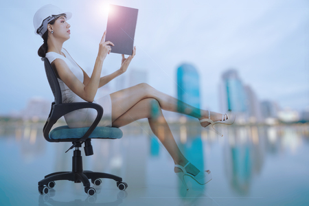 Business woman sitting on chair, holding and looking at file with blur buildings background