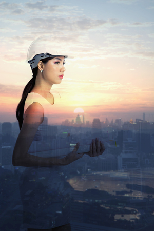 Female engineer holding paper rolls on blurry buildings background at sunset time Stock Photo