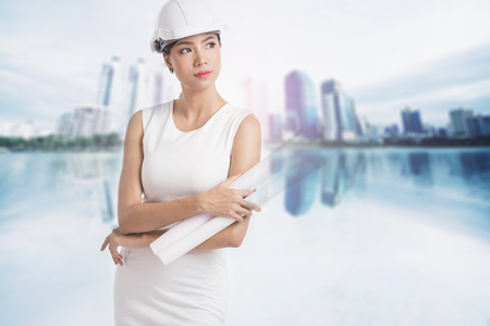 Female engineer crossing her arms and holding paper rolls on blurry buildings background Stock Photo