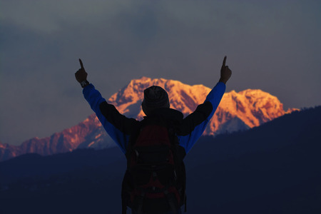 basque country: Hiker young man with backpack looking at mountain range and put hands up. Trekker man trekking in Nepal trekking route around Himalaya Mountain. Tourist traveling in holiday in the beginning of winter.