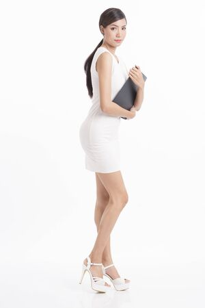 sexy asian woman: Business woman standing and holding file waring white dress on white background Stock Photo