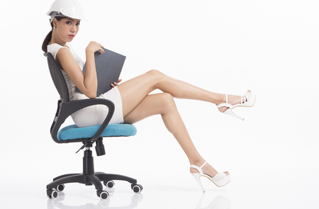 sexy asian woman: Sexy girl structural engineer sitting on chair and looking at camera on white background Stock Photo