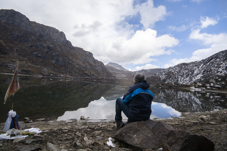 Man enjoying very much to look at blue lake with mountains background, blue sky with some clouds in day time at beginning of winter. This picture has been taken in Sikkim, India. 版權商用圖片