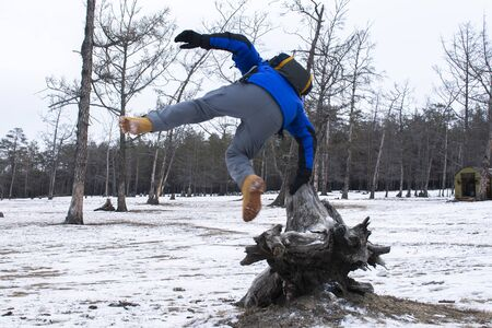 Man jumping from stump in the pine forest with snow on ground, winter in Russia, Adventure photo of traveller Banco de Imagens