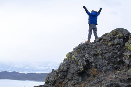 Man put his hands up on top of mountain, Lake Bikal in Russia
