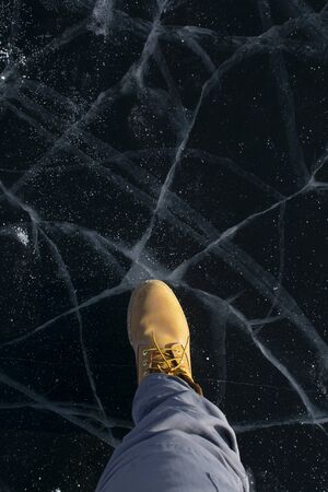 Top angle view of leg standing on broken ice in Lake Baikal, Russia
