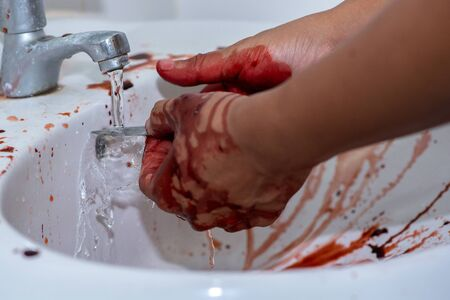 Assumption of murderer washing his hands and knife that have a lot of blood in basin